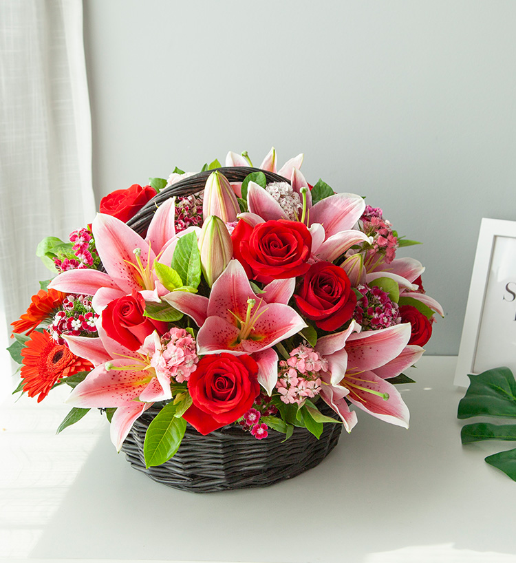 Basket of pink lilies and red roses